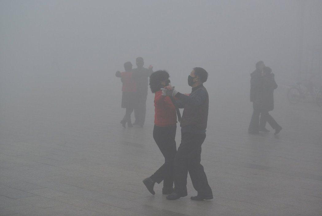 中國的大媽大伯無畏霧霾,在安徽阜陽市戶外廣場跳舞。 (路透)