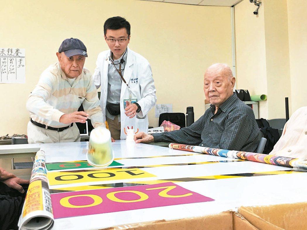 小純伯(左)在職能治療師許庭榕(中)指導下,玩紙杯娃娃推推樂遊戲。 記者鄧桂芬/...