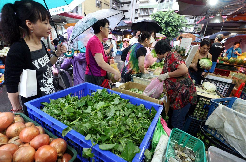 擔心菜價漲太多,民眾冒雨前往黃昏市場採買。記者侯永全/攝影