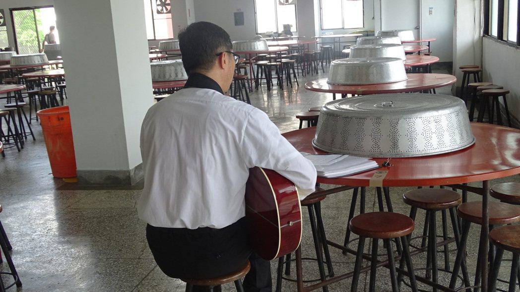 台南市政府文化局首度在在監獄進行街頭藝人考照,圖為收容人考前把握時間練習吉他。記...