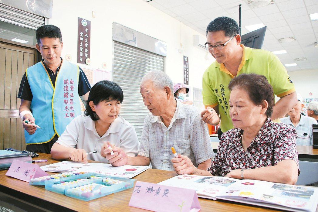 白鷺社區發展協會老師帶著長者彩繪屬於自己的人生繪本。 記者許政榆/攝影