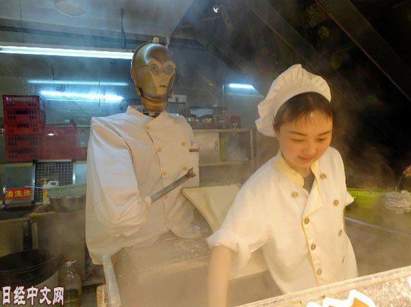 正在休息的機器人廚師和在備餐的人類員工。圖擷自日經中文網