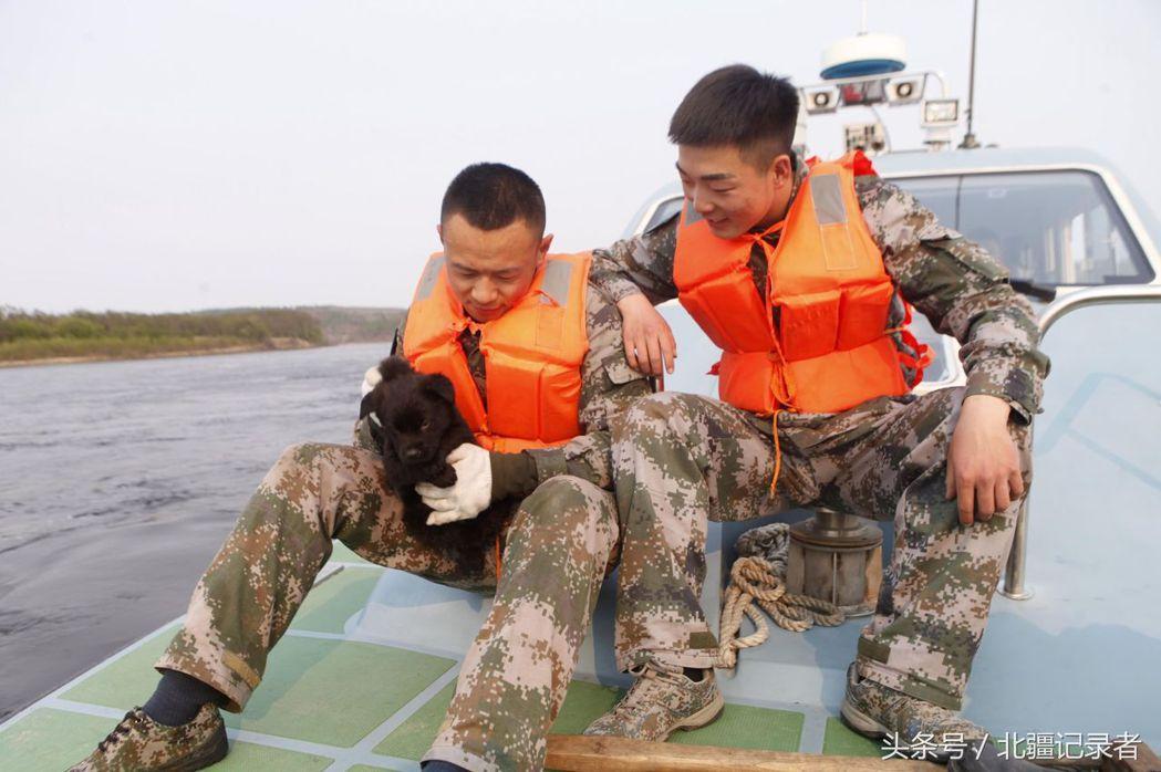 兩名水兵正查看汪星人「小黑黑」是否因為水土不服而精神不濟。圖/北疆紀錄者
