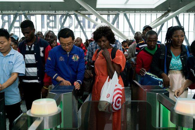 中國工作人員幫助乘客掃描車票。圖擷自紐約時報中文網