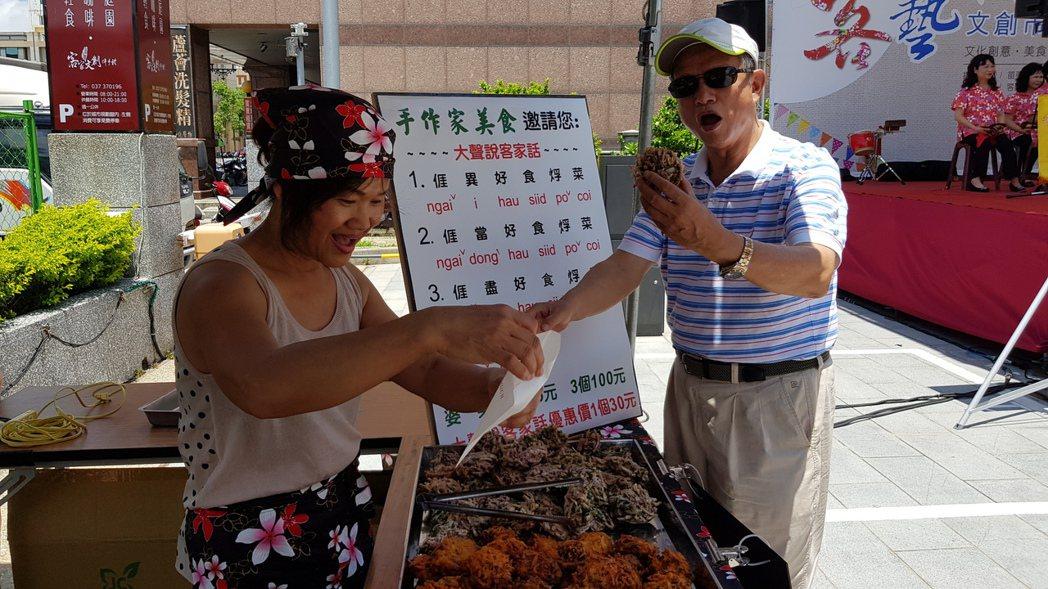 苗栗市長邱炳坤(右)大啖客家炸物美食婆菜,並與攤商一起用客語大聲說出看板上的文句...