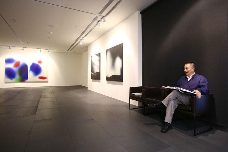 張裕能在展廳裡看著收藏的作品。記者蘇健忠/攝影