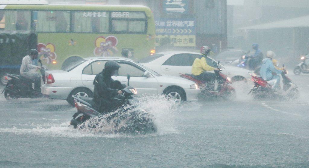 鋒面將至,請民眾要特別小心防災。圖為汐止一家大賣場前十字路口大淹水,騎士冒險涉水...