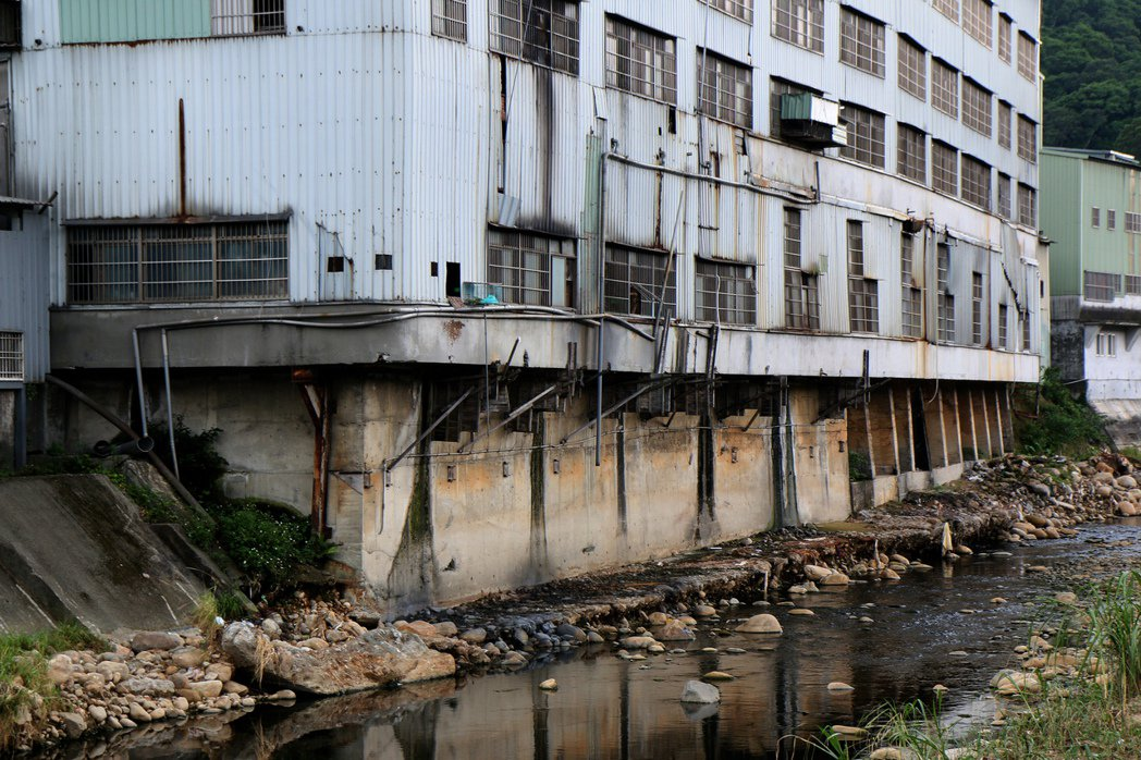 鐵皮廠房緊鄰五股坑溪邊,牆面都看得出排水的痕跡。記者王敏旭/攝影