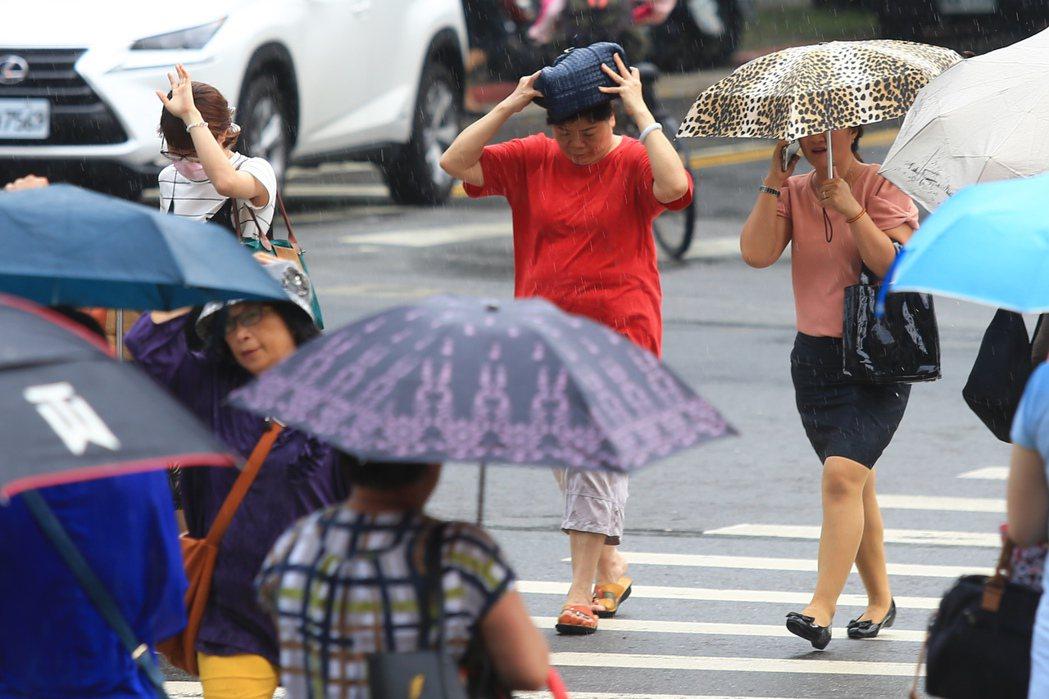台北昨天午後下起大雷雨,台大醫院周邊行人因為雨勢驟降,只好拿起包包遮雨。 記者林...