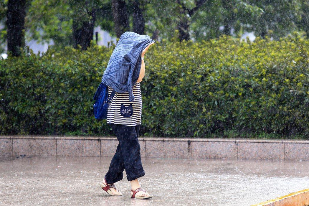 台北昨天午後下起大雷雨,戶外民眾只好拿起外套遮雨。 記者林伯東/攝影