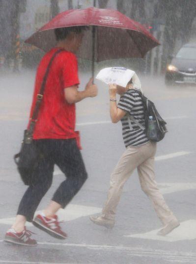 昨天午後對流旺盛,民眾外出不論有無未攜帶雨具,拔腿快跑,仍是淋得一身濕。記者陳正...