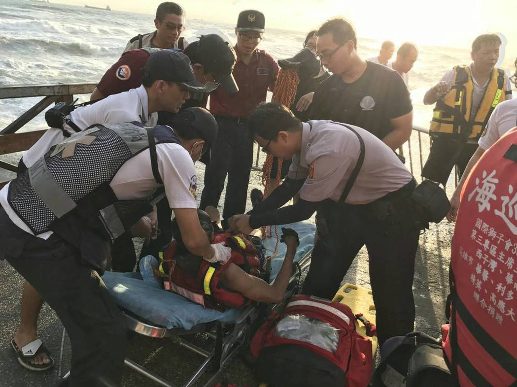 阿伯為了撿起隨身腰包,遭海浪捲走,幸好消防人員拋繩索救回一命。記者蕭雅娟/翻攝