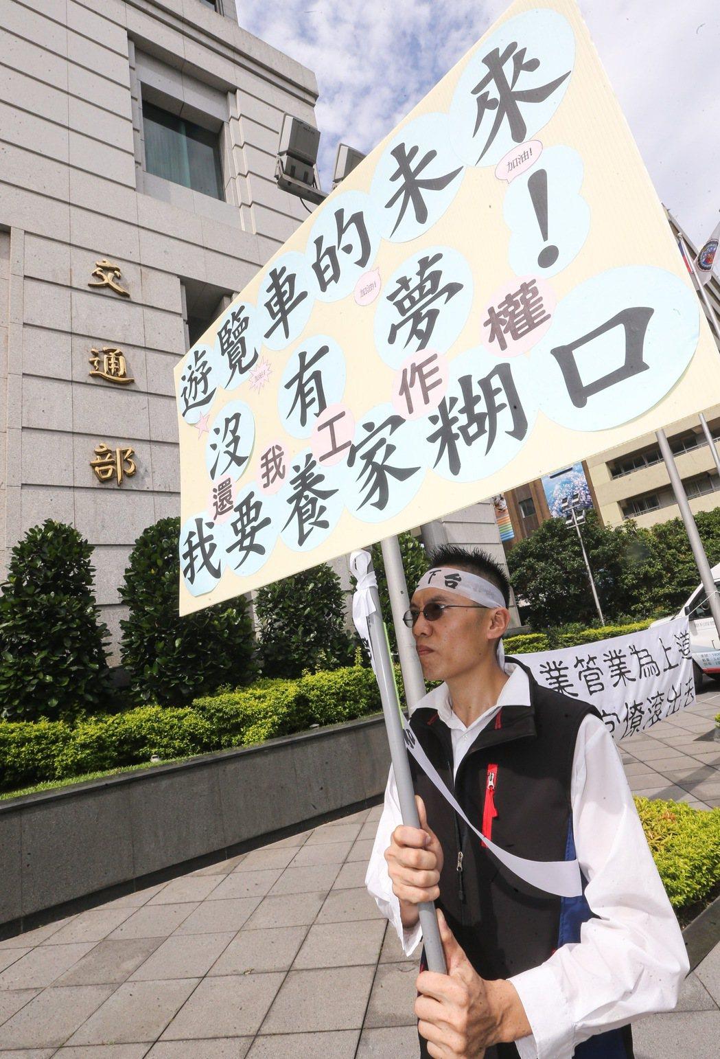 遊覽車司機在交通部前高舉標語表達訴求。記者黃威彬/攝影