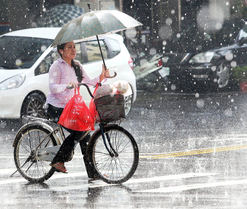一名騎乘腳踏車出外採買的外配,在滂沱大雨中,撐著傘小心翼翼地單腳划步穿越濕滑的馬...