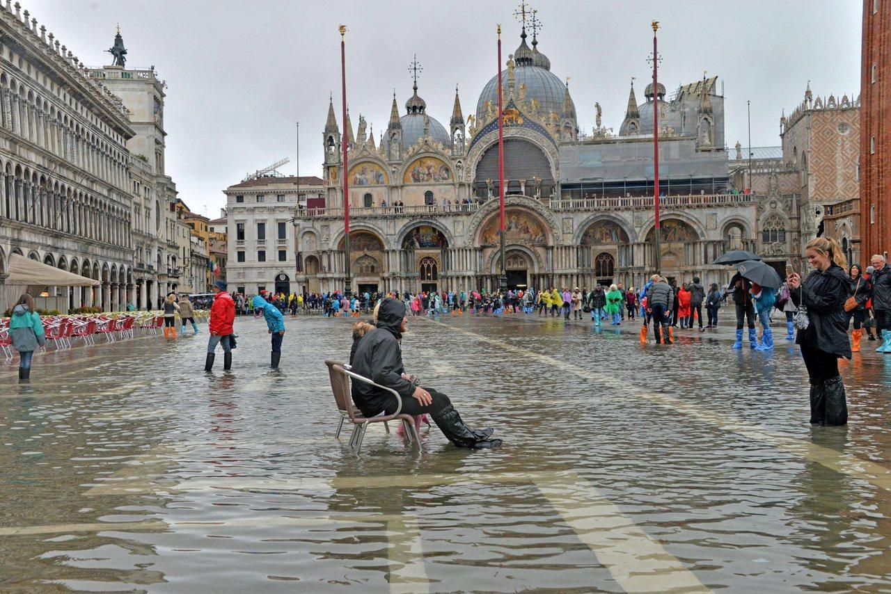 威尼斯聖馬可廣場淹水,觀光客仍是不減其樂。 歐新社