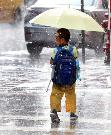 一名放學返家的小朋友在傾盆大雨中回頭張望。本報資料照/記者侯永全攝影