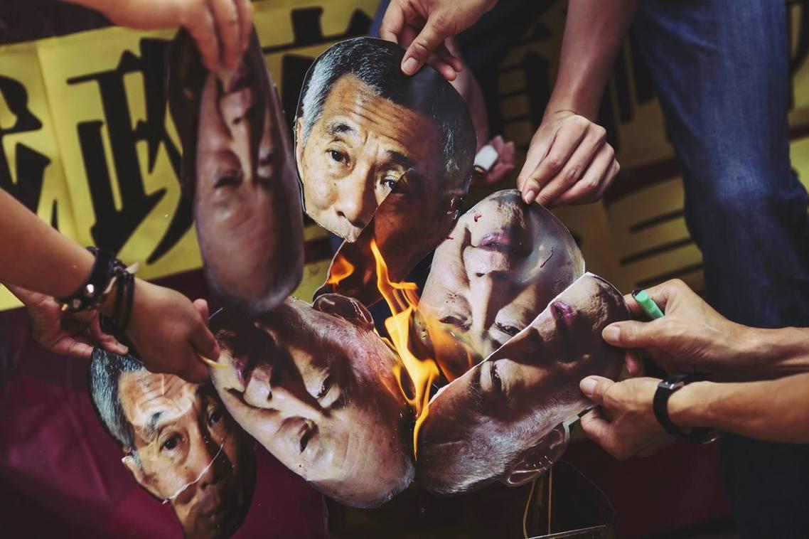 遭焚燒的李顯龍與李光耀肖像。 圖/路透社