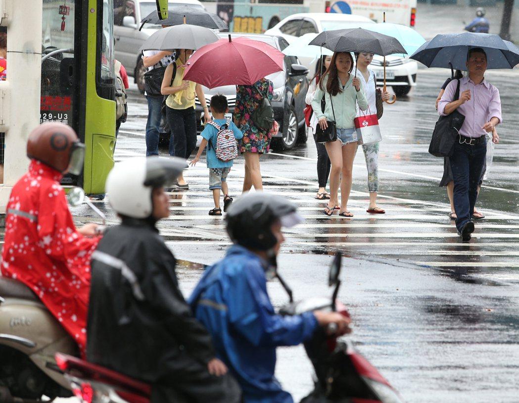 梅雨鋒面今起影響全台,民眾及騎士撐傘或穿上雨衣遮雨。記者侯永全/攝影