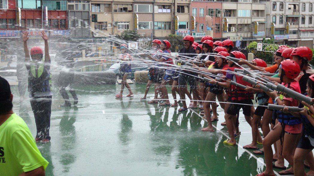 校長張錦霞(左)站在操場中央,接受畢業生們水柱齊發,猛烈洗禮。圖/野柳國小提供
