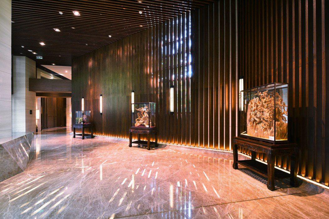 「美術帝國」在大廳長廊舉辦木雕展,每件木雕巧奪天工。 圖片提供/友友建設