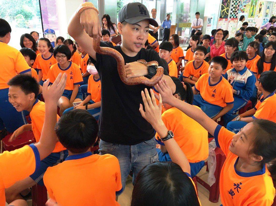 吳沁婕(中)帶著蛇與小朋友近距離接觸,小朋友又新鮮又害怕。圖/和德文教基金會提供