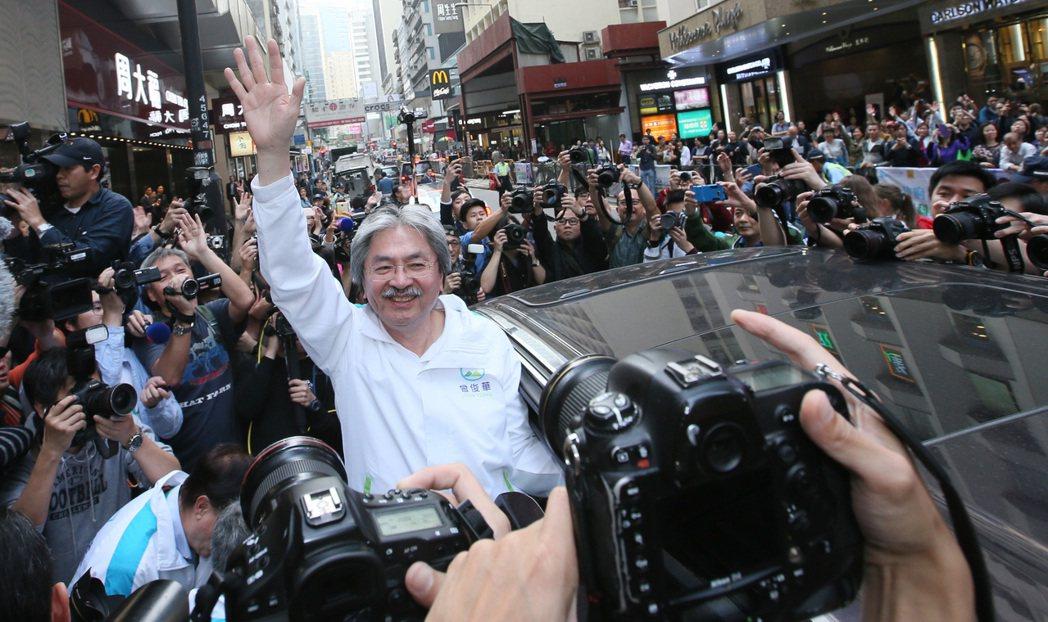 競逐香港特首失利的曾俊華(圖中白衣者)15日出席活動,笑稱自己沒想過有一天會變成...