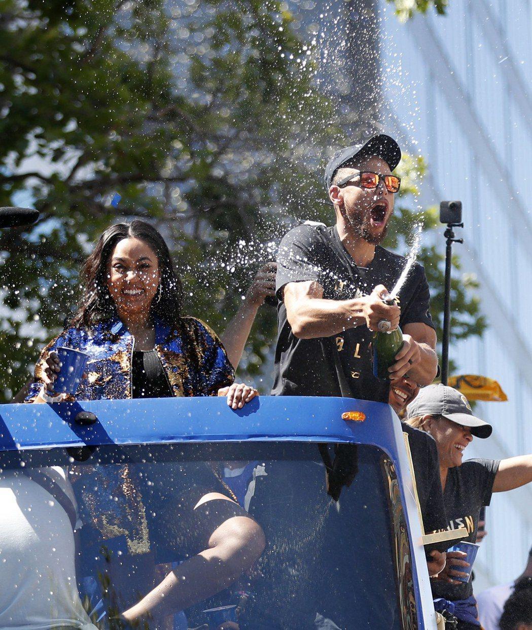 柯瑞(右)和老婆在遊行巴士上噴香檳。 歐新社