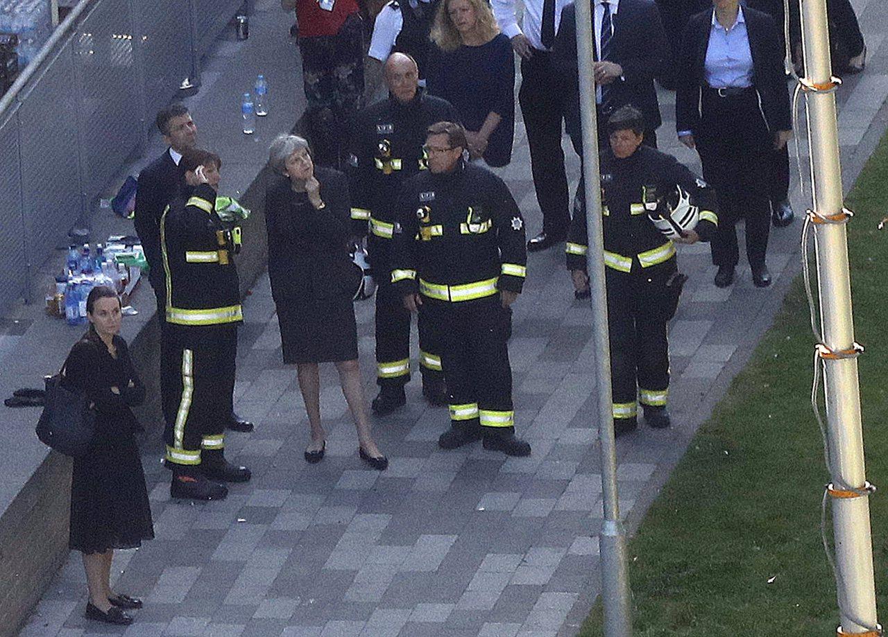 英國首相梅伊(中)15日巡視倫敦「格蘭菲塔」公寓大樓火災現場,與消防員交談。(美...