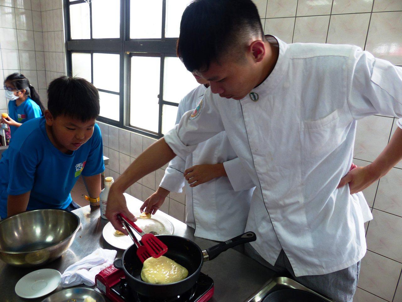 大葉大學餐旅系學生示範,小朋友專心看著如何將銅鑼燒翻面。記者凌筠婷/攝影