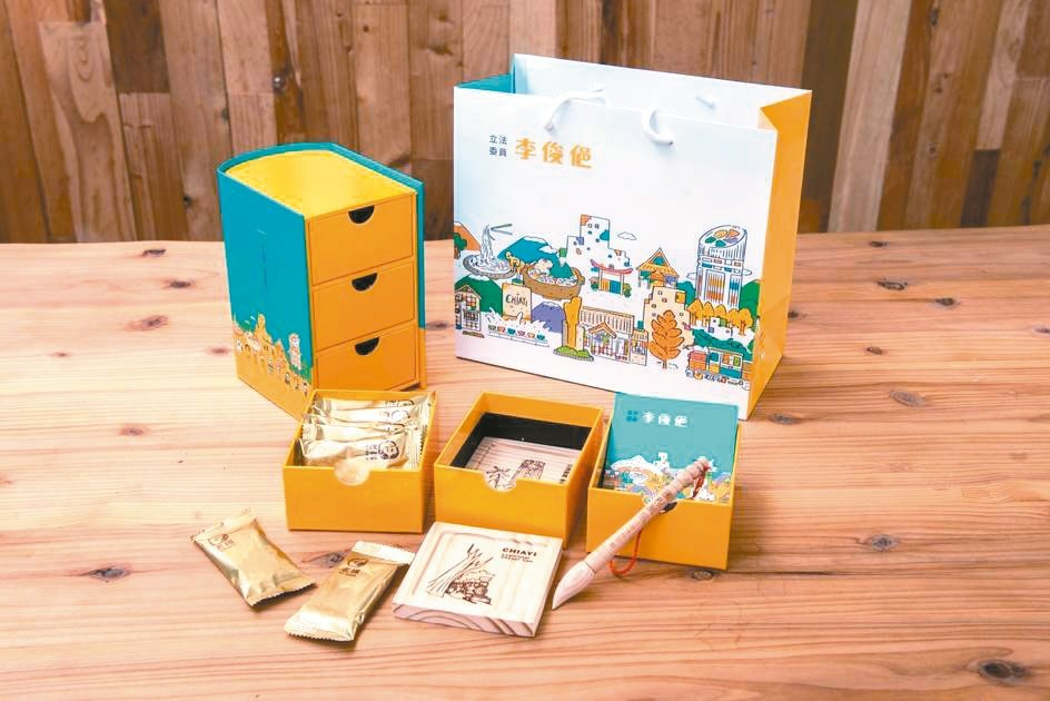嘉市立委李俊俋送精緻的書本抽屜禮盒,內有方塊酥、檜木筆、木製杯墊及便條紙,取材自...