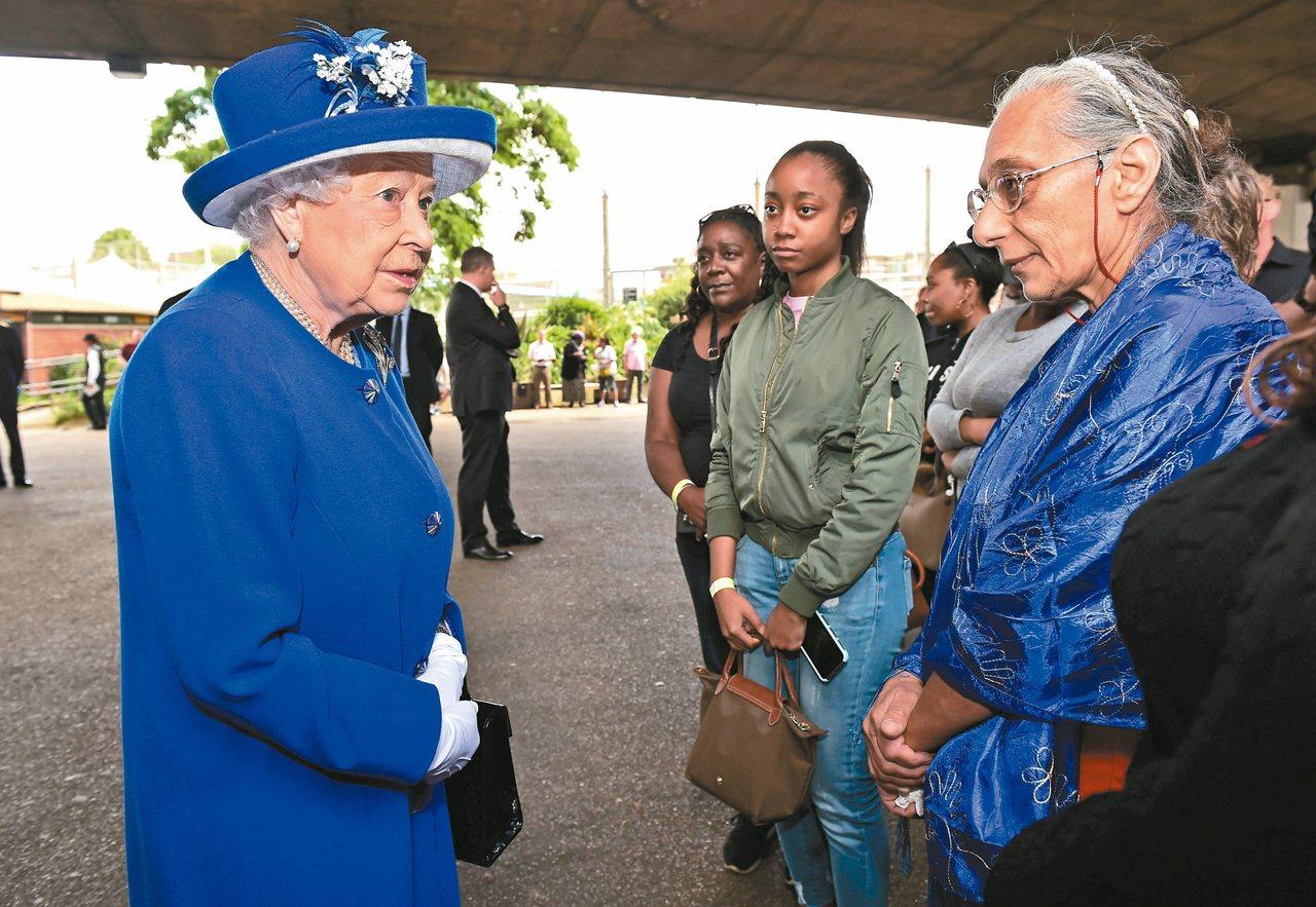 女王風範 英國女王伊麗莎白二世(左)十六日探視格蘭菲塔大樓火災的災民。 路透
