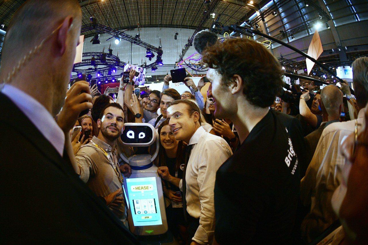 法國總統馬克宏(中)十五日在巴黎參觀科技展,與機器人和民眾自拍。 (歐新社)