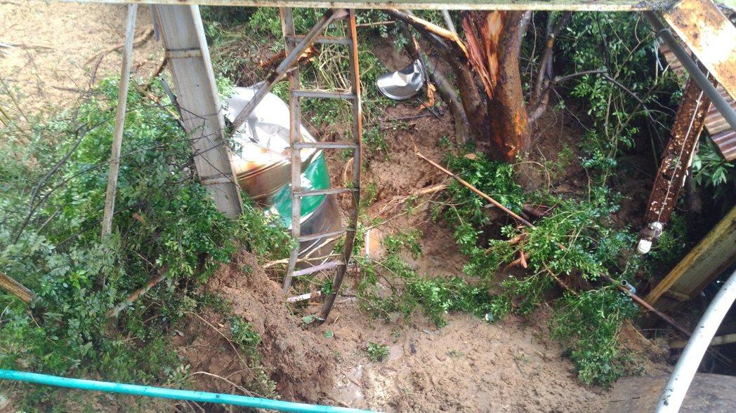 彰化縣八卦山土石鬆動下滑,民宅後面一片泥濘,水塔陷在土石流裡。記者簡慧珍/攝影