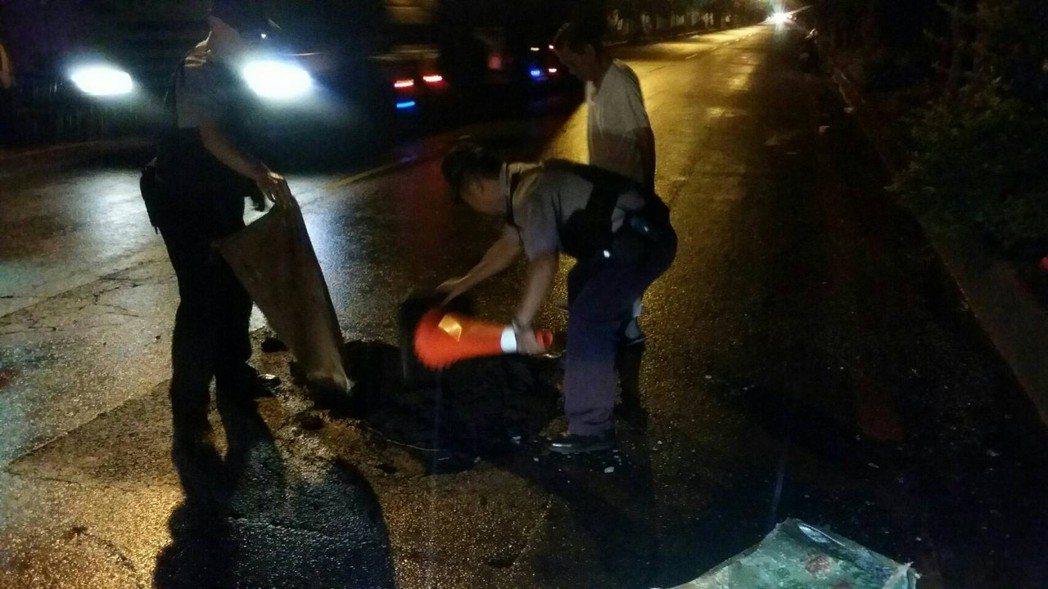 警方用交通錐底座充當耙子將瀝青鋪平。記者郭宣彣/翻攝