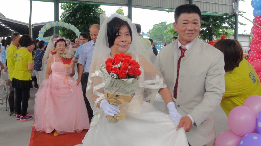 獨居的黃瓊英,兒子遠居美國,今天穿婚紗由糖廠社區協會理事長郭泰志(右)陪同參加活...