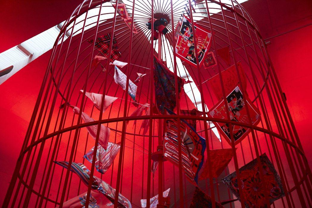 大型裝置藝術將愛馬仕絲巾放在鳥籠中,營造旗海飛揚的華麗視覺。圖/愛馬仕提供。