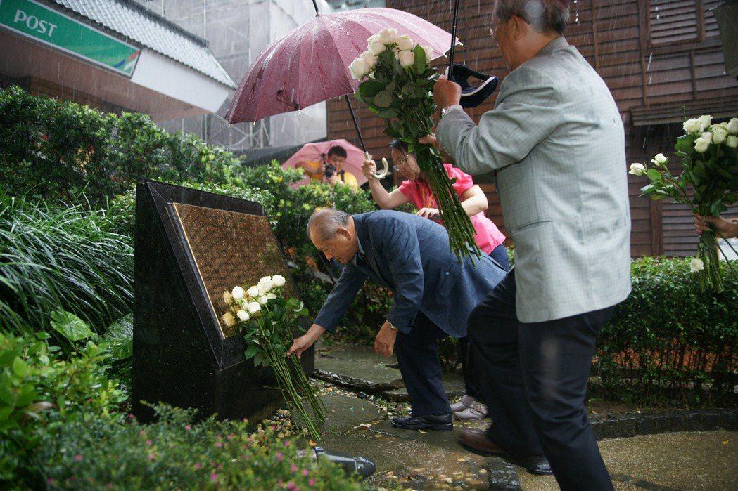 受難者家屬獻上白玫瑰悼念33名受難者,表達追思。 圖/黃金博物館提供