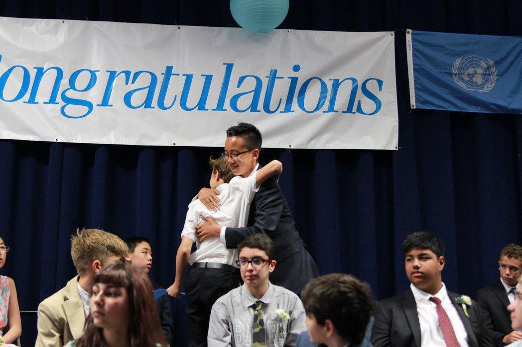 孫浩天以優異成績,畢業於聯合國國際學校。圖為他與同學激動擁抱。(記者李碩/攝影)