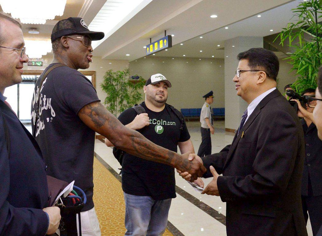 日本共同社提供的照片顯示,羅德曼(前左二)在平壤機場與送行的北韓官員握手。(路透...