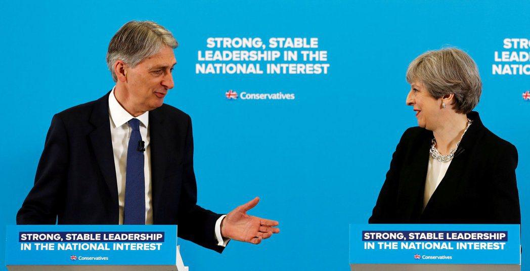 英國財政大臣韓蒙德(左)呼籲首相梅伊(右)採務實立場展開脫歐談判。(路透資料照片...