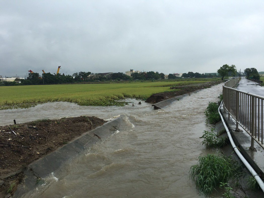 東西二圳在彰化市大竹段破堤,山洪湧進缺口處農田。記者何烱榮/翻攝