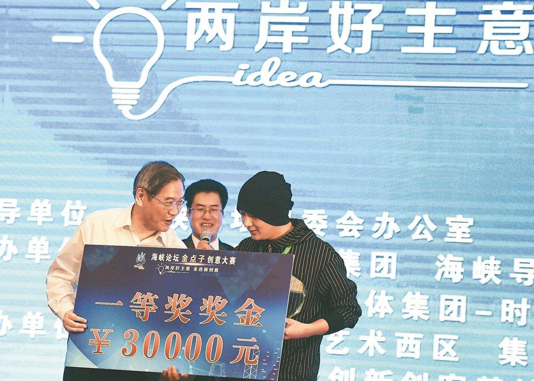 中共國台辦主任張志軍(左)昨為獲得「金點子創意大賽」一等獎的選手頒獎。 圖/中新...