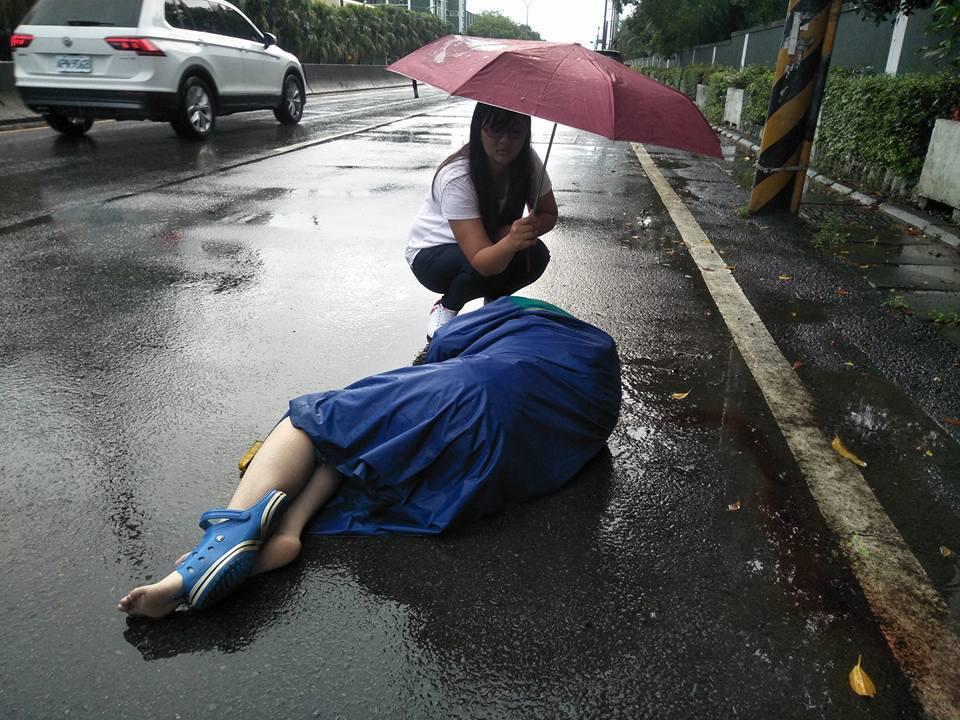 附近的熱心民眾江婉柔也跑來協助撐傘,就怕女騎士被雨淋到。記者郭政芬/翻攝