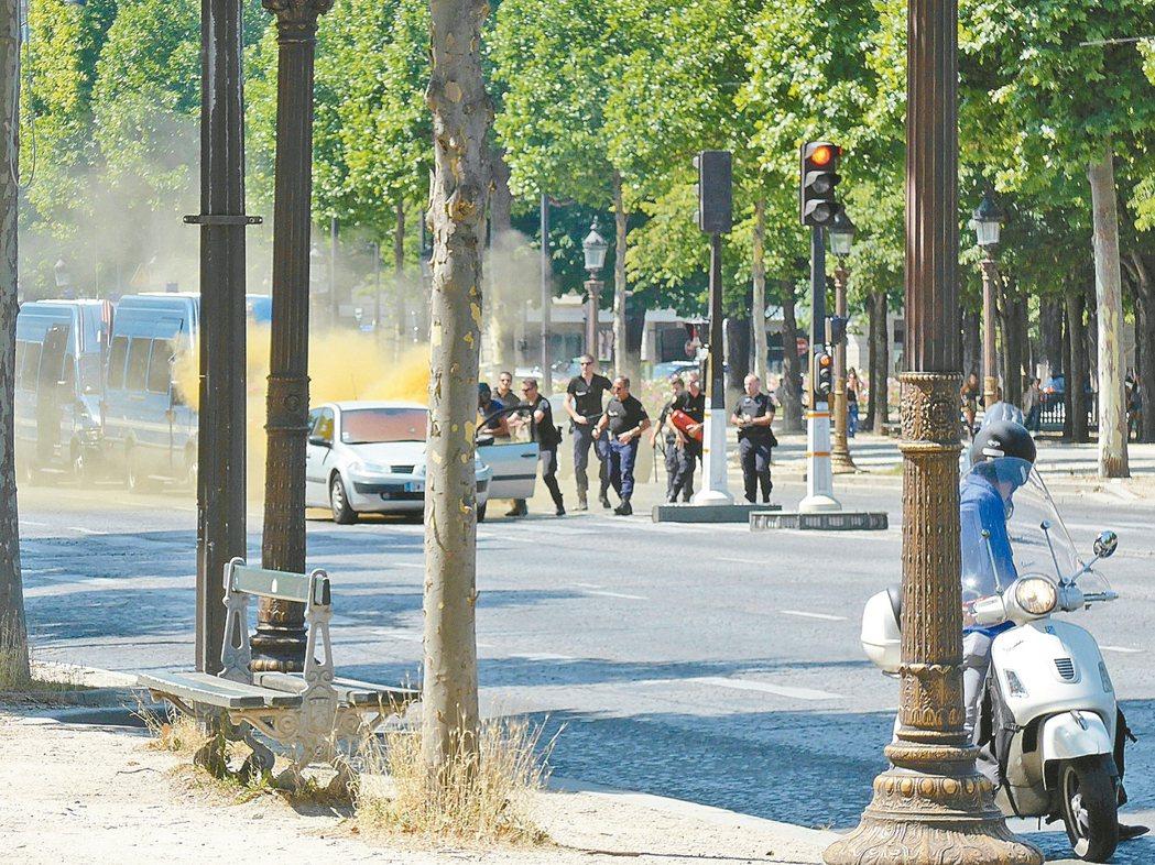 一名男子在巴黎香榭大道開車衝撞警車後死亡,他開的車子在撞擊後冒出濃煙。 美聯社