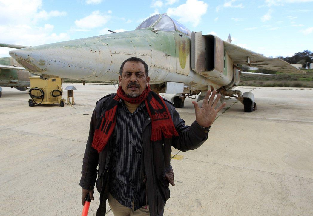 一名利比亞男子站在該國的一架舊戰機前。2011年,利比亞空軍幾乎完全放棄對抗北約...