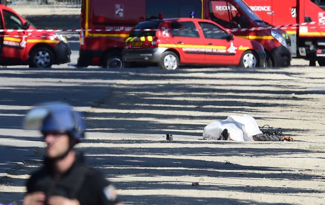 攻擊發生後,一具屍體躺臥香榭麗舍大道上。(美聯社)