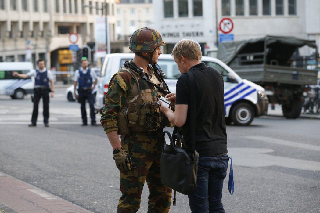布魯塞爾中央火車站發生爆炸事件,一名軍人檢查行人的身份證件。 圖/新華社