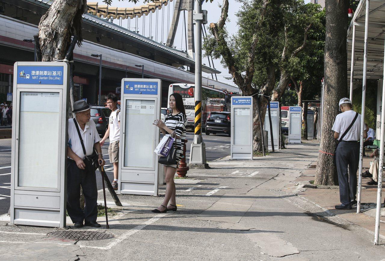 台北地區在等公車的民眾各個站到陰影處等公車順便乘涼,避免高溫日曬。聯合報資料照/...
