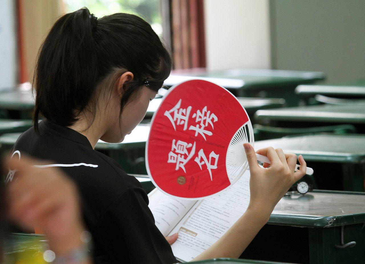 一位考生手搖扇子,把握考試前最後的時間猛K書,期盼金榜題名。圖非新聞當事人。本報...