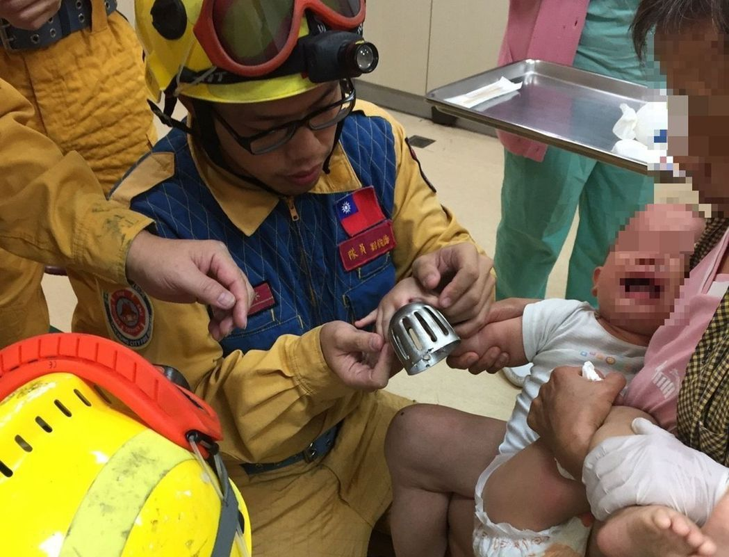 圖說一:小男童手指卡在排水孔蓋孔洞內,消防員利用破壞器材協助脫困。圖/翻攝畫面
